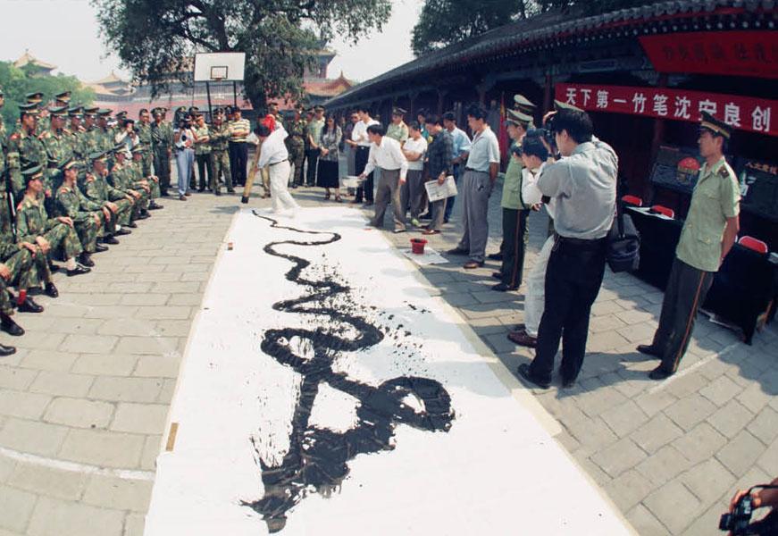 """1997年6月13日,为迎香港回归,沈安良大师在北京天安门广场国旗护卫队 现场创作8米巨""""龙""""。这是中国书法界第一位,也是唯一一位在这庄严神圣的地方举办重大活动的人。"""