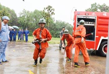 图为职工和消防人员在大雨中进行火灾扑救和逃生演练。