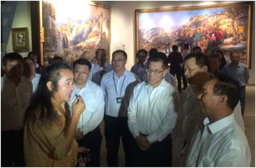 曹勇大师向西藏自治区党委副书记、西藏自治区主席齐扎拉(右)及他带领的西藏拉萨党政代表团、北京市副市长王宁(中)、北京朝阳区区长王灏(左二)等领导介绍巨幅油画《重返梁家河》